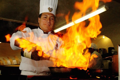 Kokk som lager brennende mat