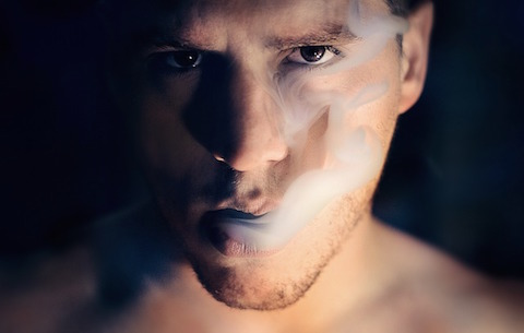Mann som blåser røyk fra munnen